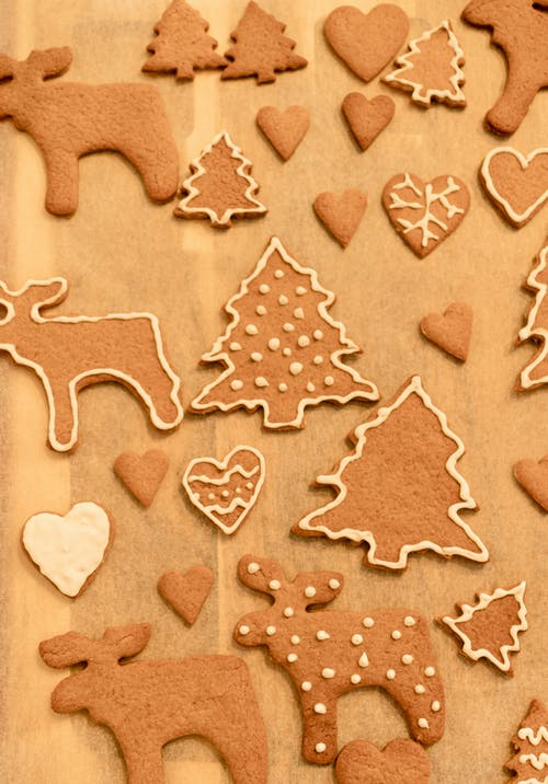 Top view composition of delicious sweet gingerbread cookies in shapes of Christmas tree and deer arranged on wooden table