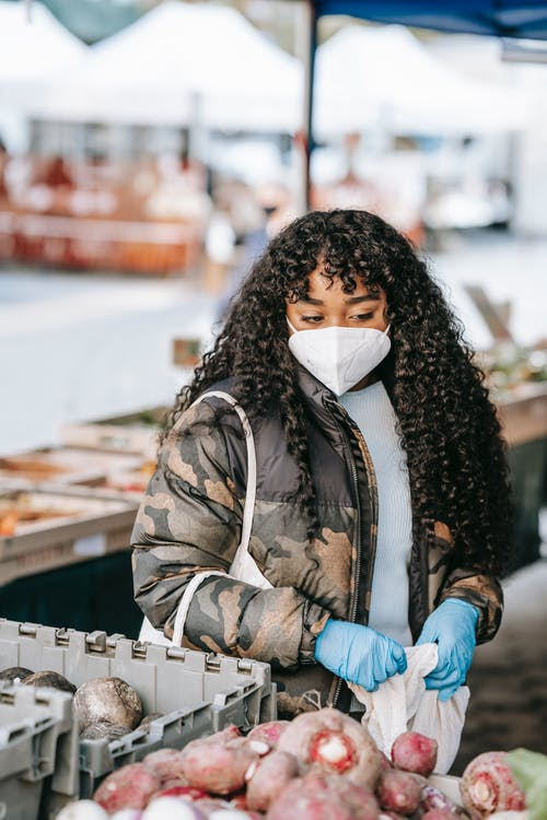 Ethnic female buyer with long curly dark hair in autumn outfit and protective mask and gloves choosing vegetables in street market