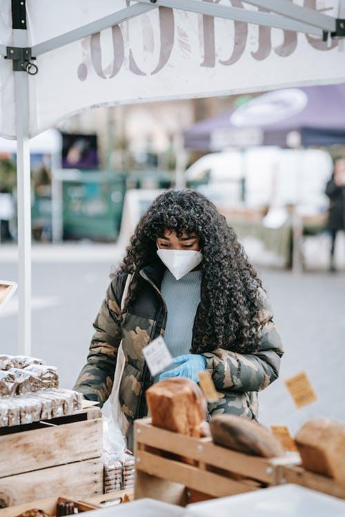 женщина в черно белом шарфе и черной куртке держит коричневую деревянную корзину