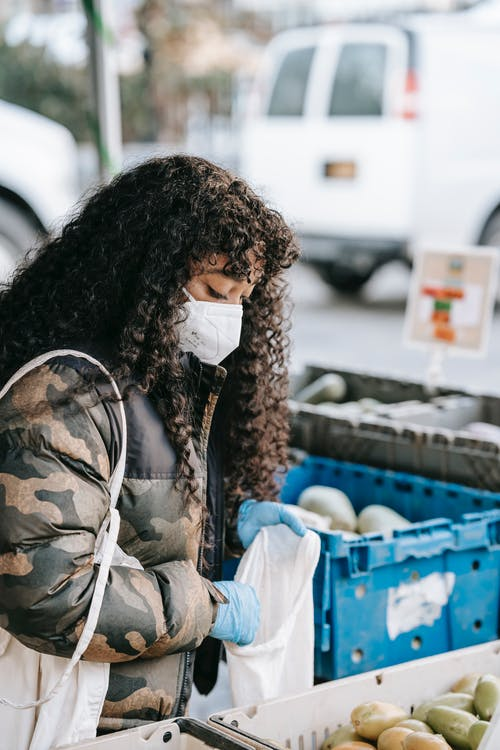 Side view of young  African American female with in protective mask and rubber gloves putting fruits in bag in outdoor grocery store