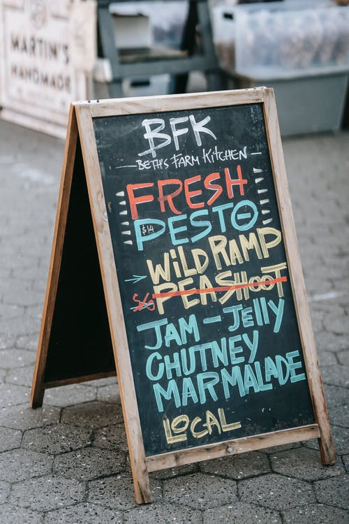 Blackboard with written menu of cafe placed on street