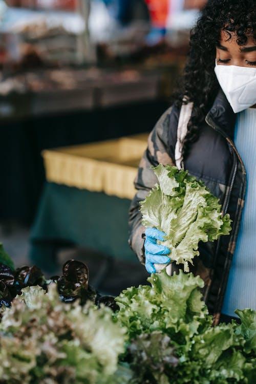 Женщина в черной куртке и синих джинсах с зелеными листьями