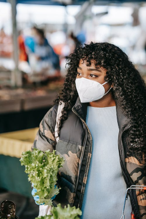 Young black woman in mask buying lettuce in market