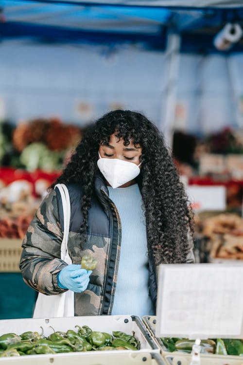 Focused African American female in protective mask and gloves picking green anaheim pepper while standing on street market on blurred background