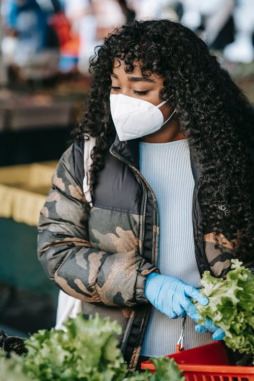Serious black woman in medical mask with lettuce in market