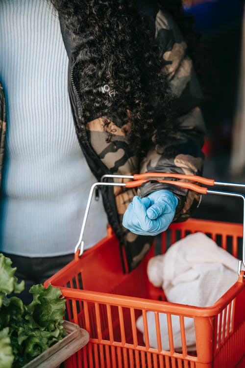 Unrecognizable female buyer wearing glove standing with grocery basket at stall with greens while choosing products in market during pandemic