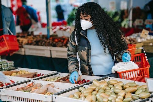 Black woman choosing vegetables in supermarket
