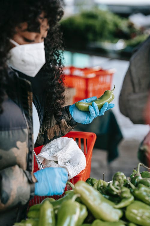 Crop concentrated African American female in respirator and gloves picking ripe capsicums while doing groceries in supermarket