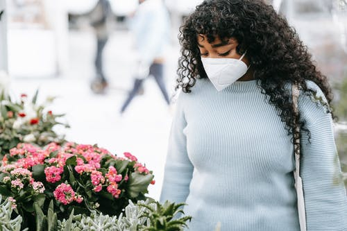 Crop black woman standing near stall with blooming flowers