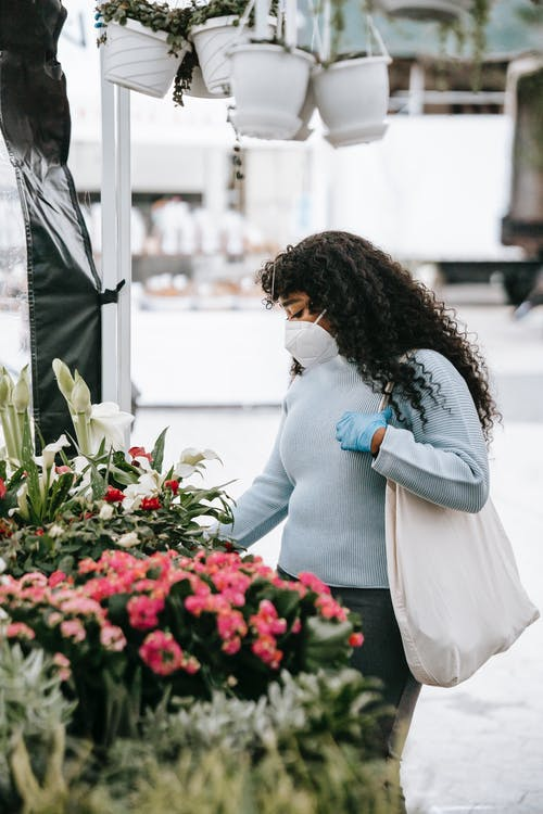 Concentrated African American female wearing blue sweater mask and gloves choosing blooming flowers presented on stall in outdoor floral market