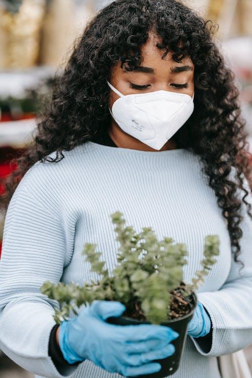 Crop black woman choosing potted plants in market