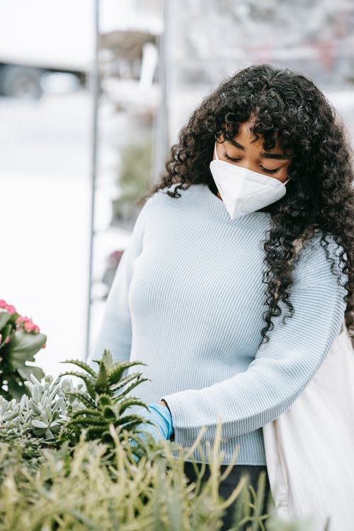 Focused African American female in respirator and gloves picking verdant potted plants in outdoor floral market