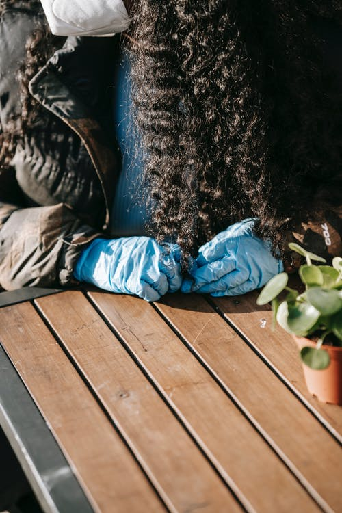 Crop unrecognizable female with long curly hair in casual clothes sitting at wooden table with potted plant in sunny day