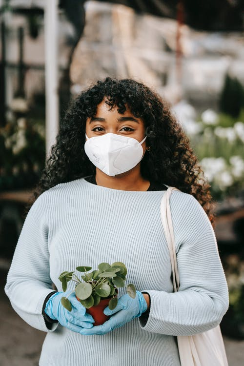 Black woman in protective mask and gloves standing with potted plant