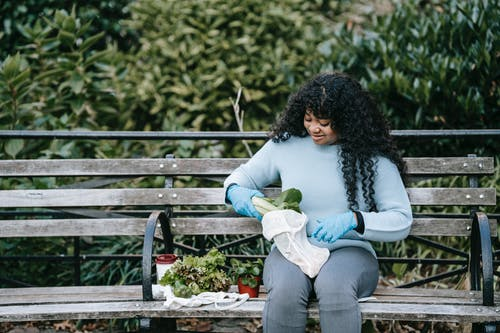 Cheerful African American woman sitting on wooden bench and putting fresh salad in eco friendly sack against green bushes in daytime