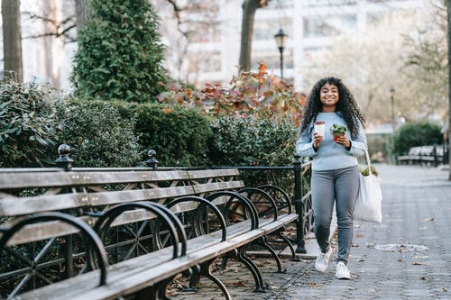 Full length of smiling young black lady strolling with shopping bag with greenery and to go cup with coffee and potted plant near bench and shrubs in daytime in park
