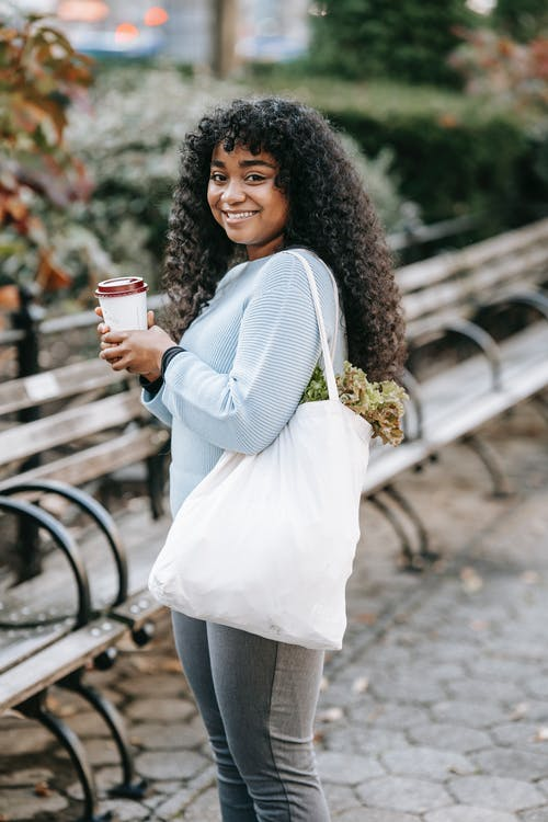 Black lady with shopping bag and takeaway drink in park