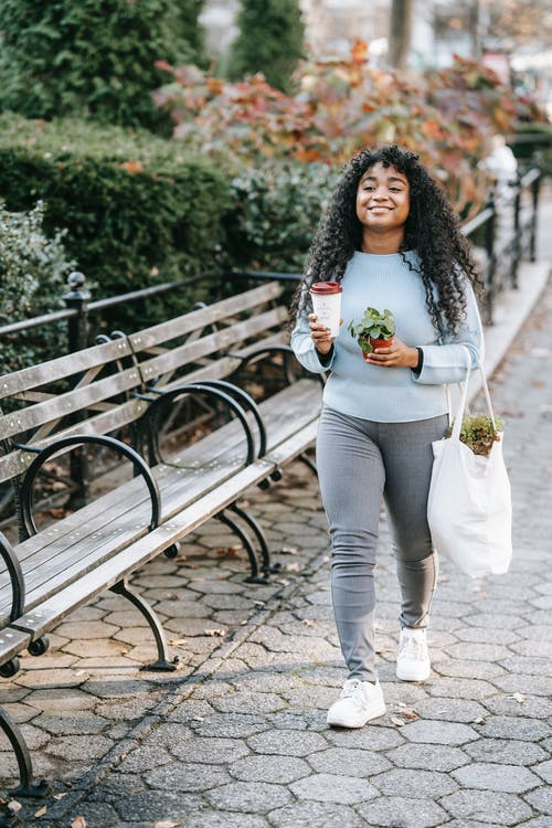 Full body of happy young black lady walking with shopping bag with greenery and paper cup with drink with potted green plant near bench and shrubs in park in daytime