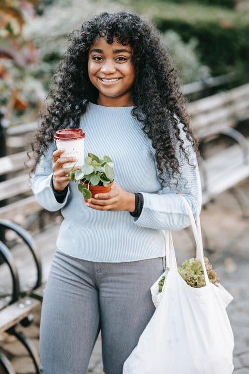 Smiling African American female standing with shopping bag with greenery and paper cup with coffee and potted plant in street near bench and bushes in daylight and looking at camera