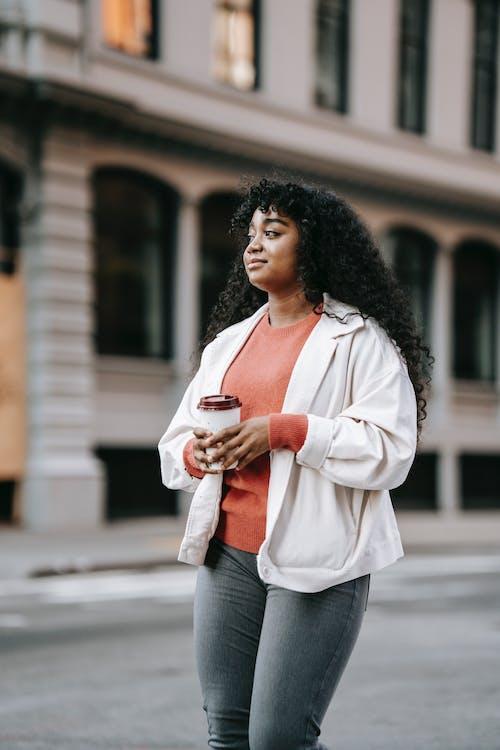 Black lady walking in town with takeaway drink in street