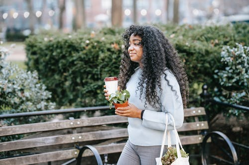 Black woman in park with takeaway drink and potted plant
