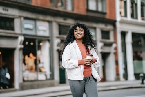 Cheerful black woman with takeaway coffee walking on street