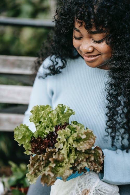 Crop black woman holding lettuce salad in park