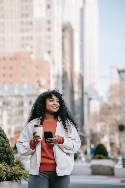 Happy African American female wearing casual clothes standing with coffee to go and browsing mobile phone on modern city street while looking away with smile