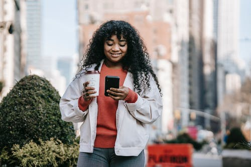 Smiling black woman with takeaway coffee browsing smartphone on street