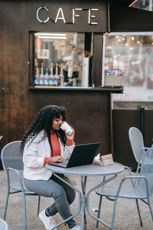 Positive African American female in casual wear enjoying fresh takeaway coffee and browsing netbook while sitting at table in outdoor cafeteria