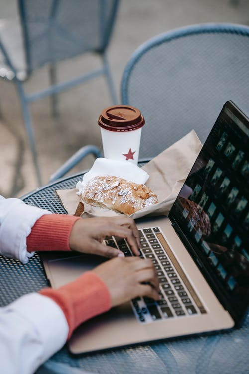 Crop faceless black woman working on laptop in outdoor cafe