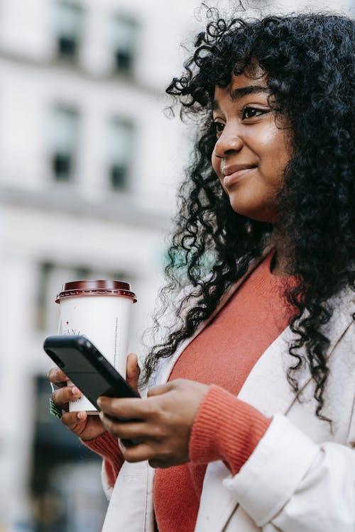 Crop happy black woman browsing modern smartphone on street