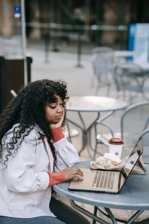 Thoughtful black woman working on laptop in street cafe