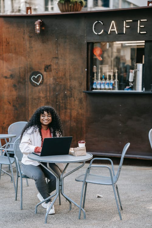 Full length joyful African American female in casual clothes browsing netbook while sitting at table in outdoor cafeteria with coffee to go and delicious sandwich