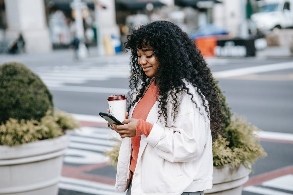 Cheerful adult African American female in white jacket surfing mobile phone while standing with takeaway coffee on modern city street
