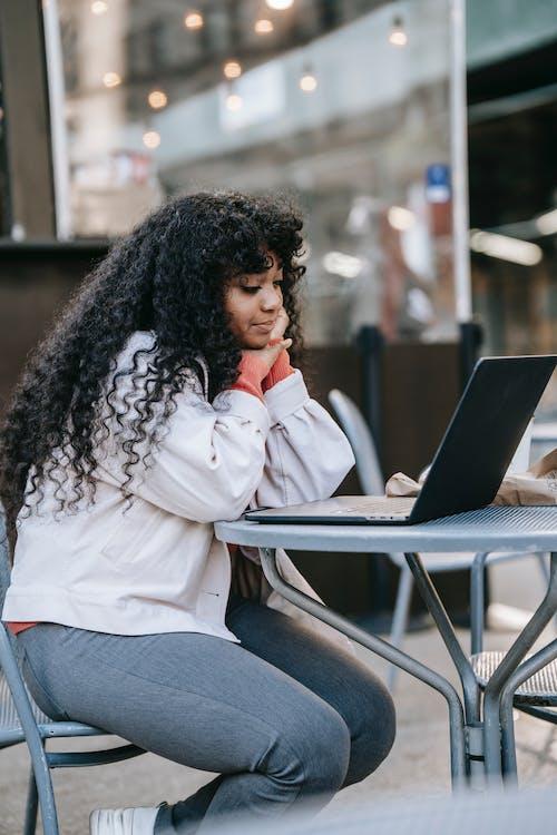 Frau Im Weißen Hemd, Das Auf Stuhl Mit Macbook Sitzt