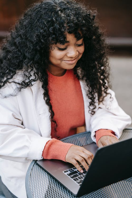 Smiling black woman browsing laptop in street cafe