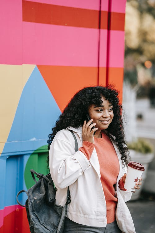 Cheerful African American female wearing casual clothes having pleasant conversation via mobile phone while standing with takeaway coffee near colorful wall on street