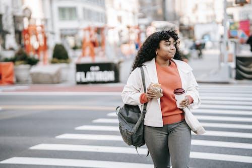 Friendly black woman with takeaway coffee crossing road in city