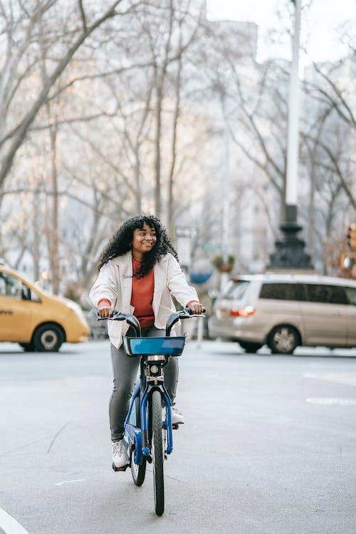 Joyful black woman riding bicycle on street