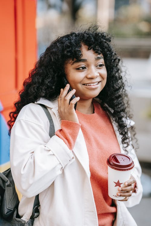 Content African American female with curly hair enjoying takeaway coffee and having conversation via mobile phone while standing on street