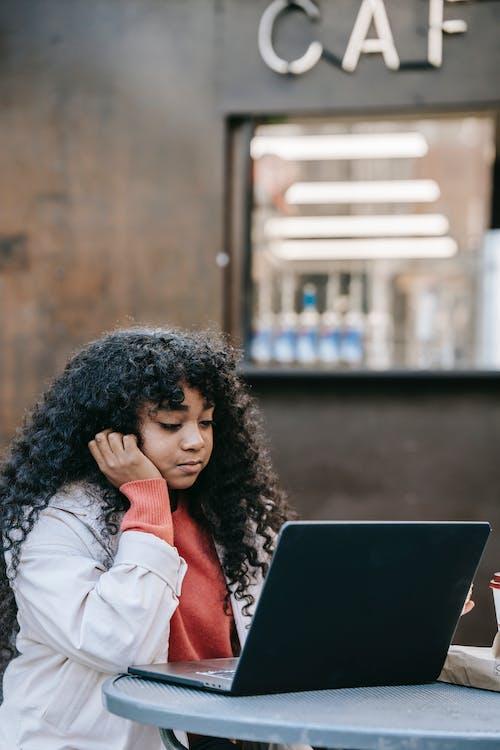 Frau In Der Weißen Jacke Unter Verwendung Des Schwarzen Laptop Computers