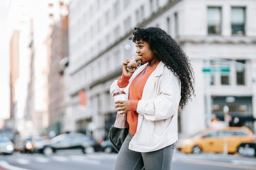 Black woman biting sandwich and crossing road