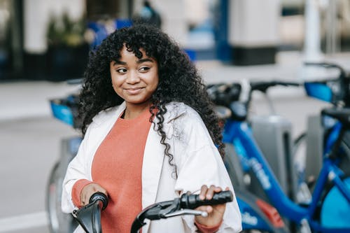 Smiling African American female cyclist wearing casual outfit standing with bicycle near bicycle sharing station on modern city street