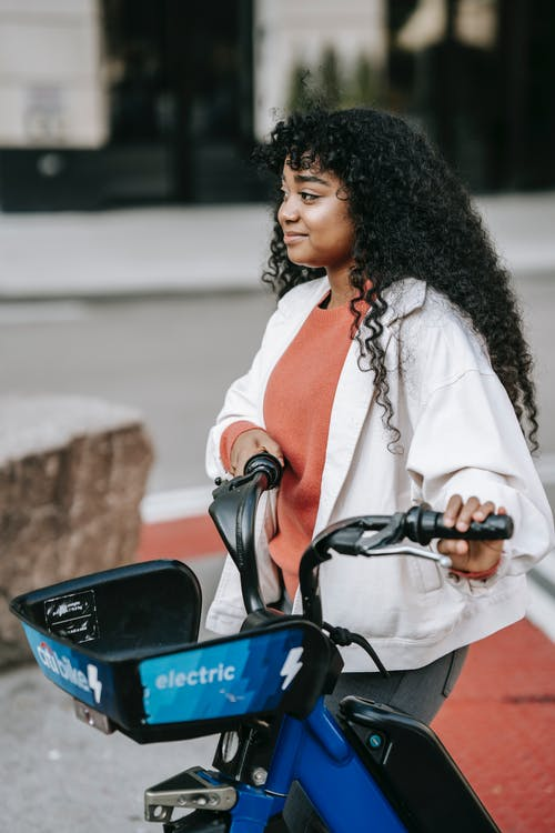 Content black woman walking with bicycle on street