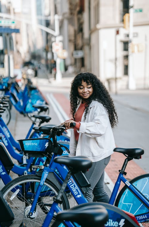 Side view glad African American female with long curly hair renting bicycle in public bicycle sharing station on modern city street