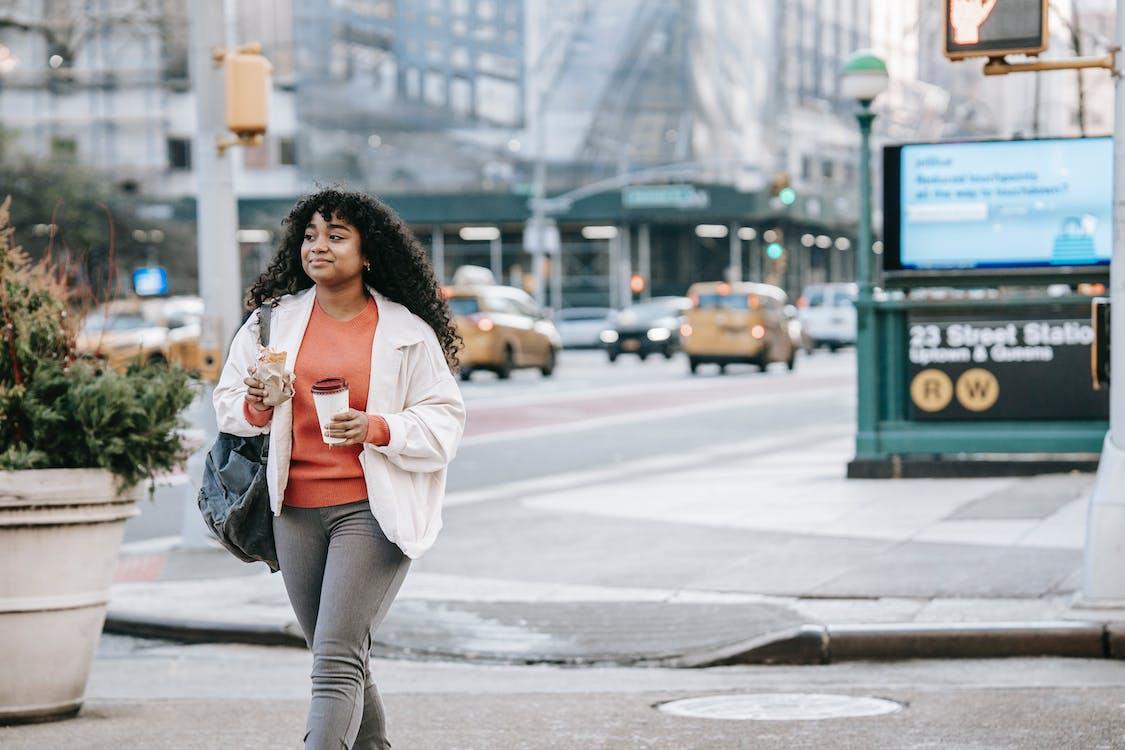 Black woman with takeaway coffee and sandwich walking on street