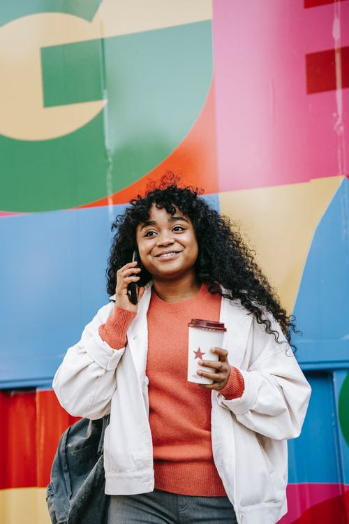 Cheerful African American female in casual wear with takeaway coffee having conversation via mobile phone while standing against colorful wall on street