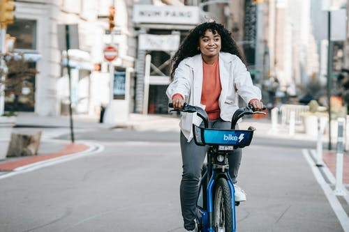 Content African American female in casual wear riding bicycle on modern city street in daylight