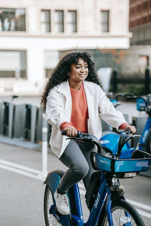 Joyful black woman riding bicycle on city road